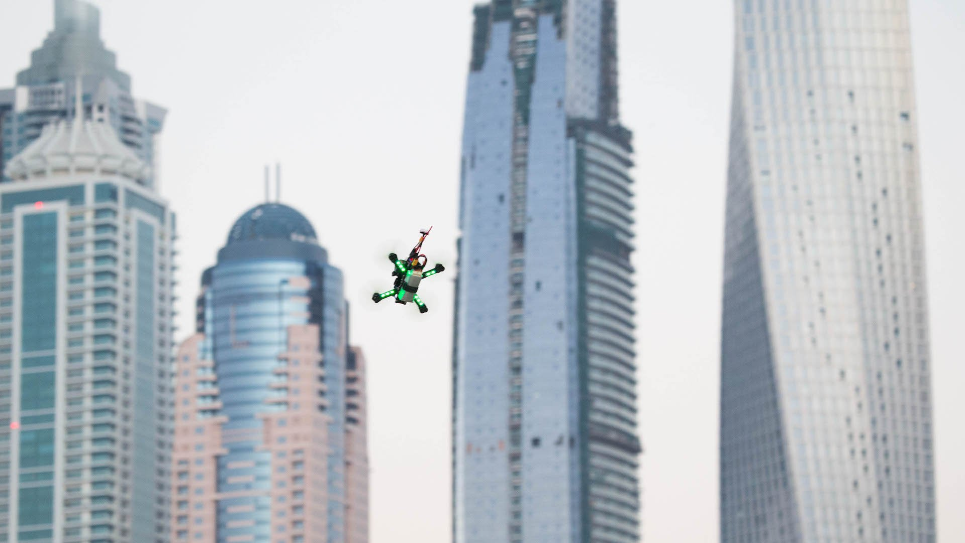 A drone flies around the track in front of the Dubai's Marina skyline during the World Drone Prix drone racing championship in Dubai, United Arab Emirates, on Saturday, March 12, 2016. Teams compete for the global champion purse of total prizes of $1 million by navigating drones at over 100kms an hour around a track which features multiple pathways, kinetic and static obstacles designed to push pilots to their limits. Photographer: Razan Alzayani/Bloomberg
