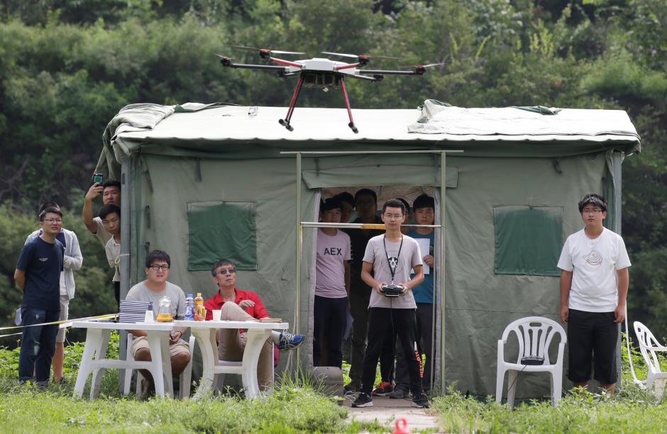 A trainee flies a drone next to a China Civil UAS (Unmanned Aerospace Surveillance) Pilot Flight examiner (in red) during his examination for the license from AOPA CHINA (Aircraft Owners and Pilots Association) at LTFY drone training school on the outskirts of Beijing, China August 14, 2017. REUTERS/Jason Lee