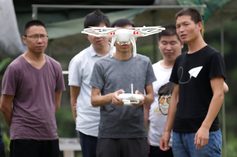 A trainee learns to fly a DJI drone next to the instructor at LTFY drone training school on the outskirts of Beijing